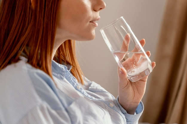 Porträtfrau, die glas wasser trinkt