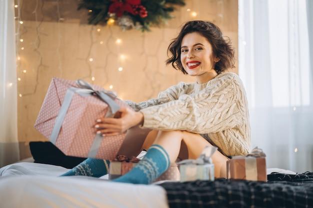 Porträtfrau, die im bett mit geschenken herum sitzt
