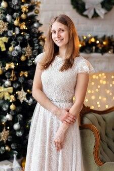 Porträtfrau, die kleid sitzt, das nahe dem weihnachtsbaum sitzt
