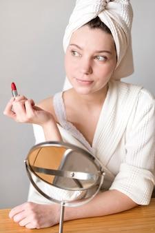 Porträtfrau, die lippenstift anwendet