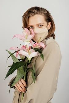 Porträtfrau, die maske trägt und blumenstrauß hält