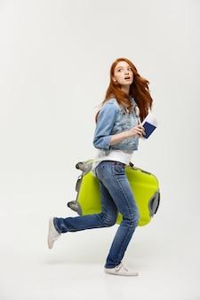 Porträtfrau, die mit einem großen koffer und einem pass zu den ferien hält und läuft.