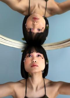 Porträtfrau, die mit spiegel aufwirft