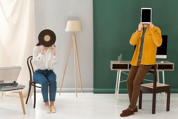 Porträtfrau, die musik an der abholung und am mann mit tablette hört