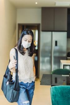 Porträtfrau, die schutzmaske hält, die handy hält