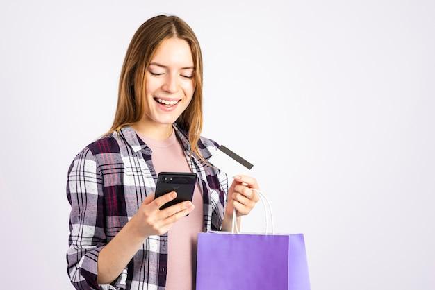 Porträtfrau, die telefon betrachtet und eine tasche hält