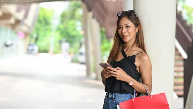 Porträtfrau im schwarzen unterhemd unter verwendung des smartphones beim stehen mit dem tragen einer einkaufstasche nach dem fertigen einkauf am städtischen einkaufszentrum mit der unscharfen straße