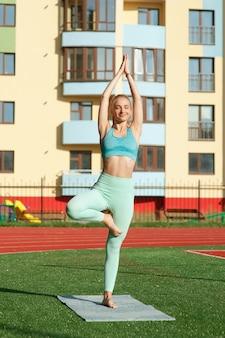 Porträtfrau im stadion beim yoga