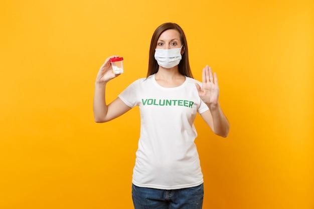 Porträtfrau im weißen t-shirt mit der aufschrift grüner titelfreiwilliger, sterile gesichtsmaske mit pillendroge einzeln auf gelbem hintergrund. freiwillige kostenlose hilfshilfe, wohltätigkeits-gnaden-gesundheitskonzept