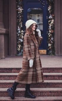 Porträtfrau in voller länge in einem mantel auf dem hintergrund einer weihnachtlich geschmückten stadt