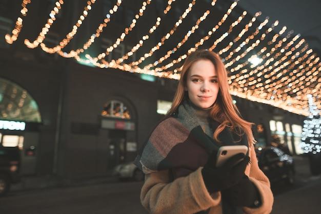 Porträtfrau in warmer kleidung benutzt ein smartphone, schaut auf den bildschirm und lächelt bei einem abendspaziergang