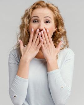 Porträtfrau lacht und bedeckt ihren mund mit den händen