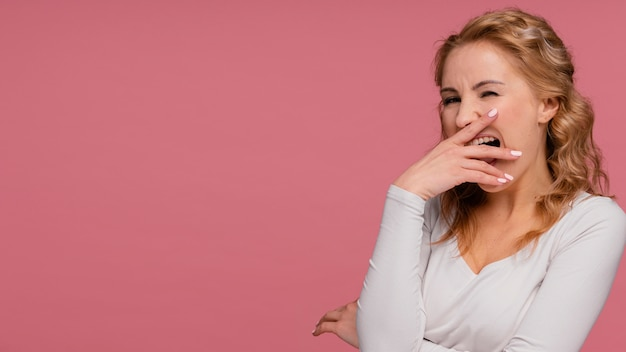 Porträtfrau lacht und bedeckt ihren mund