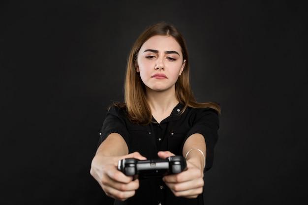 Porträtfrau mit joystick auf schwarzer wand
