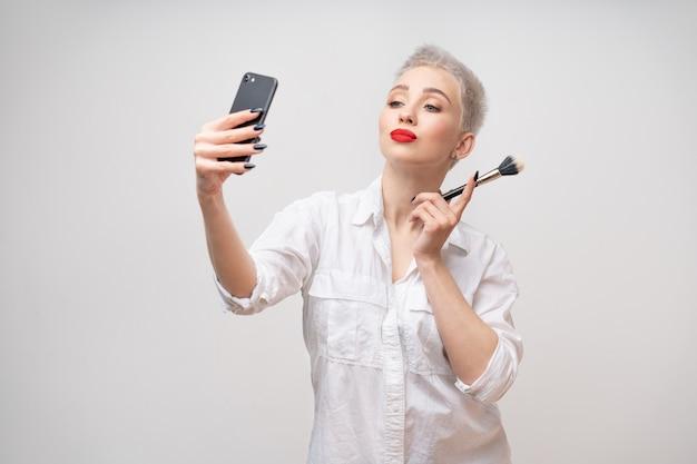 Porträtfrau mit kurzen haaren mit make-up-pinsel in der hand studio shot
