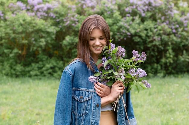 Porträtfrau mit lila blumenstrauß
