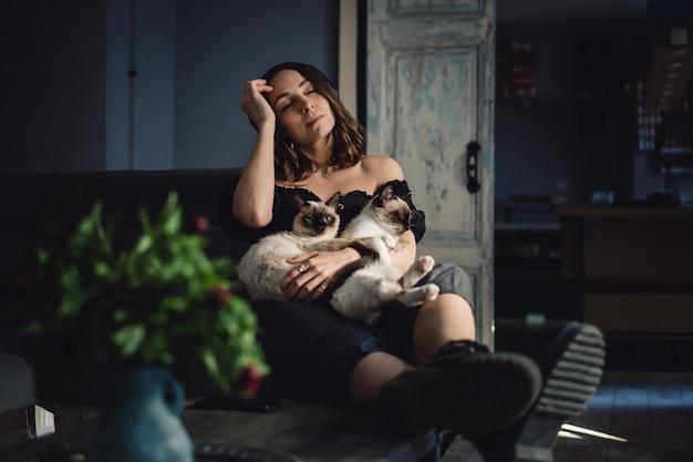 Porträtfrau mit siamesischen katzen