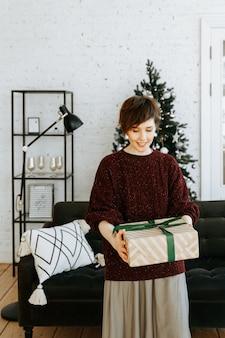 Porträtfrau mit weihnachtsgeschenk zu hause