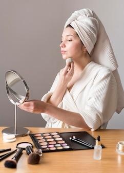 Porträtfrau schminken mit schwamm im spiegel