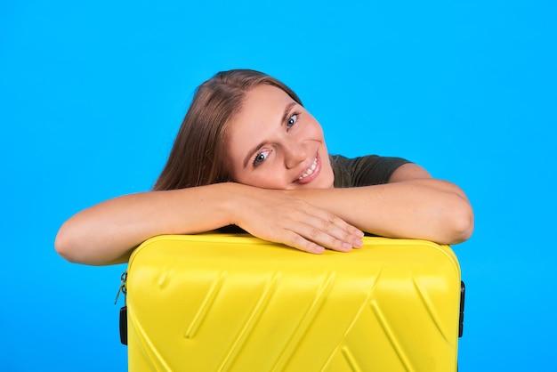 Porträtfrau sitzen mit gelbem gepäck
