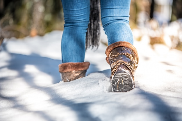 Porträtfrauenstiefel auf einer straße mit schnee beim wintergehen