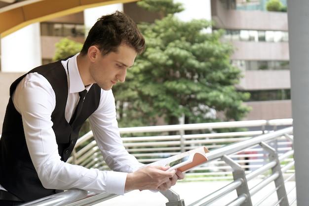 Porträtgeschäftsmann, der im geschäftsbereich steht und zeitschrift liest.