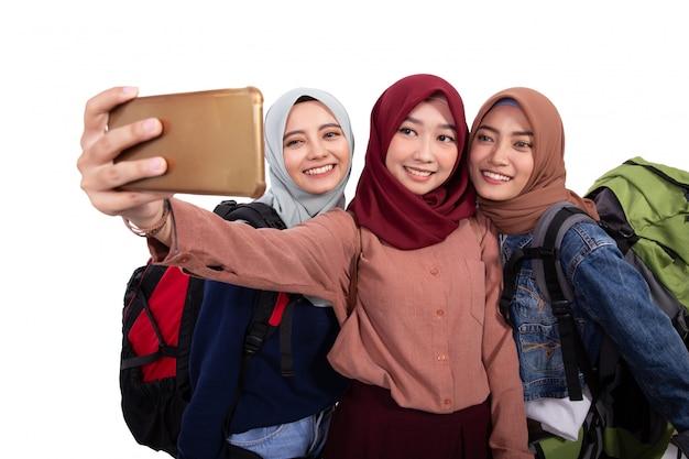 Porträtglück des hijab-reisenden selfie zusammen mit smartphone