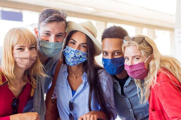 Porträtgruppe der jungen glücklichen freunde, die gesichtsmaske während der covid-pandemie tragen