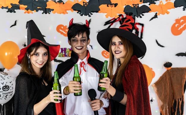 Porträtgruppe von freunden asiatische junge erwachsene leute feiern halloween-party. sie tragen halloween-kostüme, singen ein lied und jubeln. halloween feiern und internationales feiertagskonzept