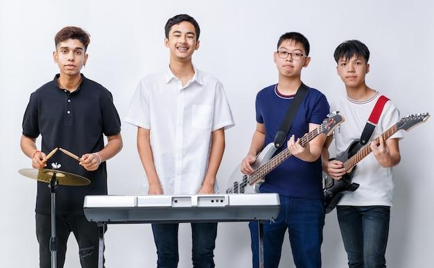 Porträtgruppenaufnahme von vier jugendlichen musikern, die ein instrument halten und die kamera einzeln mit weißem hintergrund betrachten. gruppenaufnahme eines jungen gitarristen, bassisten, keyboarders und schlagzeugers
