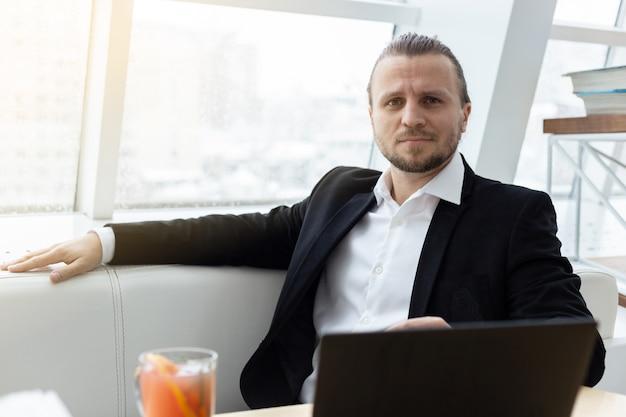 Porträtieren sie einen ernsthaften müden mann, der am tisch mit laptop im modernen innenraum sitzt.