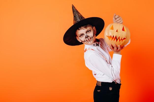 Porträtjunge im teufelmaskerademake-up und -hut, die einen kürbis zeigen. halloween