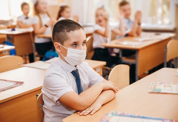 Porträtkind mit gesichtsmaske während des coronavirus in der schule