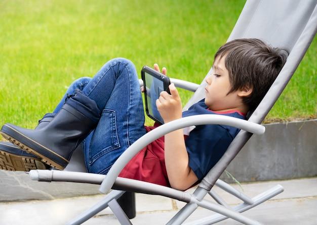 Porträtkind mit spiel auf tablette, ein junge, der spaß beim betrachten von cartoons auf digitaler tablette hat, kind, das auf roacking stuhl sitzt, der am wochenende im garten im frühling oder sommer entspannt