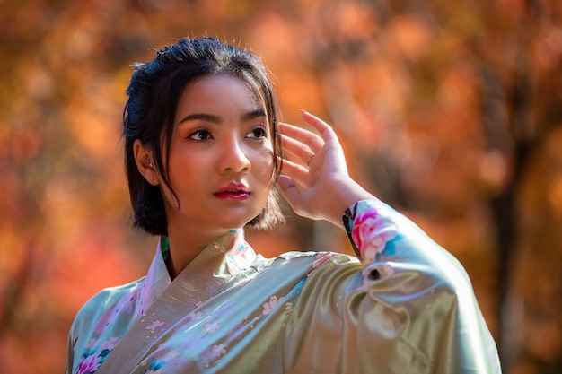 Porträtkopf schoss junge asiatische frau, die japanische kleiderkimonomodegeschichte trägt, die im park in der herbstsaison in japan steht