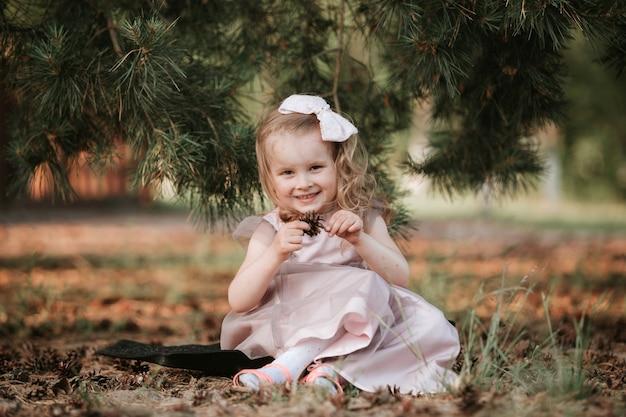 Porträtmädchen draußen. süßes mädchen im wald spazieren. erstaunliches kleines mädchen in einem kleid, das auf natur lustig ist.