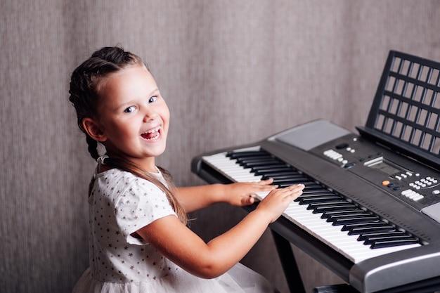 Porträtmädchen in einem weißen kleid, das lernt, einen elektronischen synthesizer zu spielen