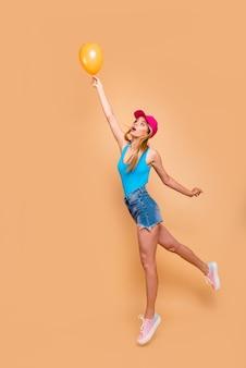 Porträtmädchen in voller länge, das mit luftballon wegfliegt