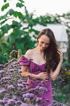 Porträtmädchen mit langen haaren in lila blumen. gehen sie in den blumengarten. mädchen und blumen. floristik.