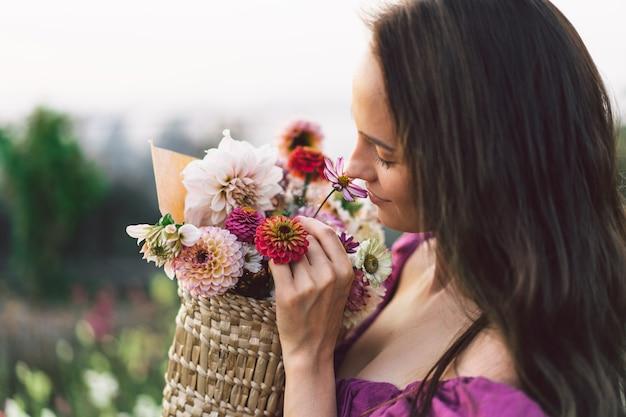 Porträtmädchen mit langen haaren mit einem blumenkorb. gehen sie in den blumengarten. mädchen und blumen. floristik.