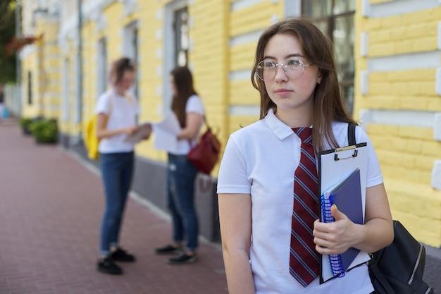 Porträtmädchenstudentenjugendlicher in der brille binden weißes t-shirt mit rucksack. hintergrund gelbes backsteingebäude, gruppe von studenten