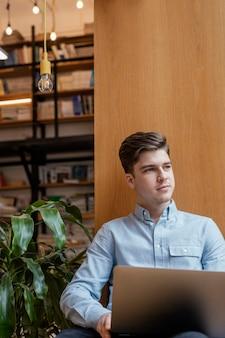 Porträtmann, der am laptop arbeitet
