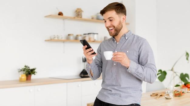Porträtmann, der kaffee trinkt, während handy überprüft