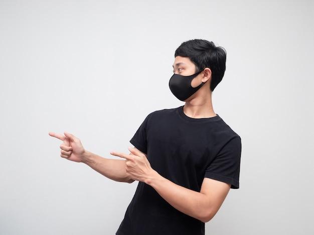 Porträtmann, der maske mit doppeltem zeigefinger trägt und auf die linke seite auf weißem hintergrund schaut