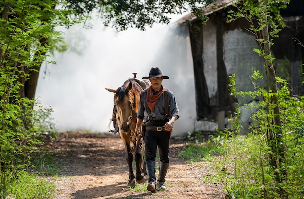 Porträtmann, der mit pferdebaum als cowboy geht