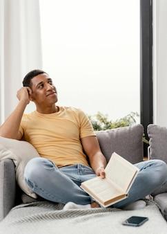 Porträtmann, der zu hause beim lesen entspannt