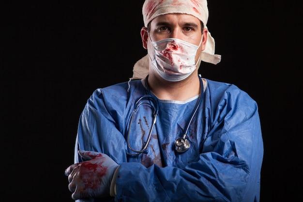 Porträtmann im arztkostüm für halloween mit blut an den händen. mysteriöser und gefährlicher arzt.