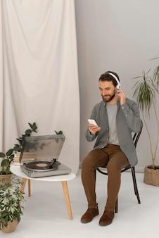 Porträtmann mit kopfhörern, die musik auf handy hören
