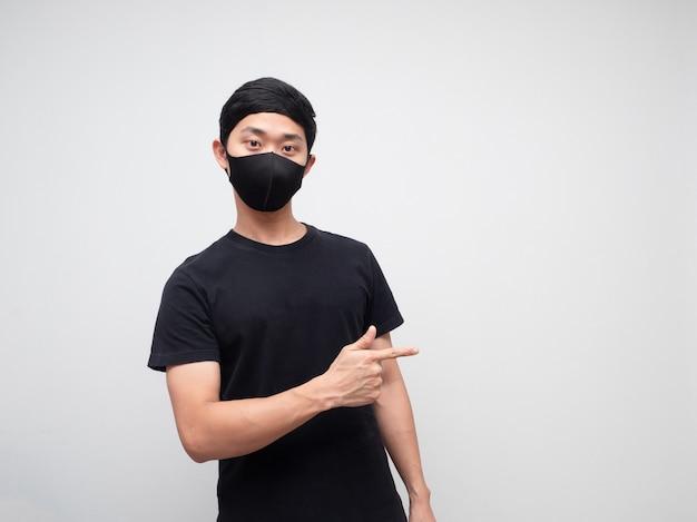 Porträtmann mit maske zeigt mit dem finger auf die rechte seite und schaut in die kamera auf weißem hintergrund
