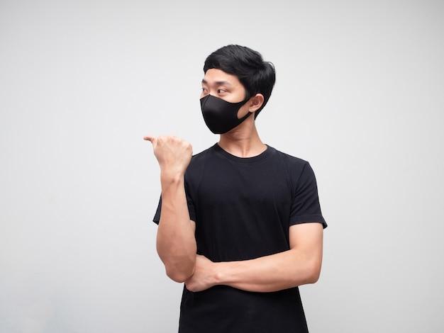 Porträtmann mit maske zeigt mit dem finger und schaut auf die linke seite auf weißem hintergrund